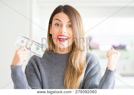 Young beautiful woman holding 20 dollars bank note at home screaming proud and celebrating victory and success very excited, cheering emotion