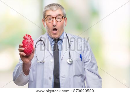 Handsome senior cardiologist doctor man holding heart over isolated background scared in shock with a surprise face, afraid and excited with fear expression