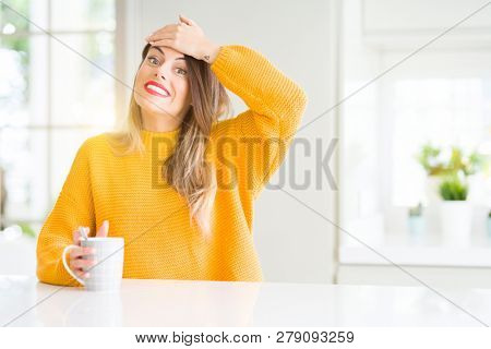 Young beautiful woman drinking a cup of coffee at home stressed with hand on head, shocked with shame and surprise face, angry and frustrated. Fear and upset for mistake.