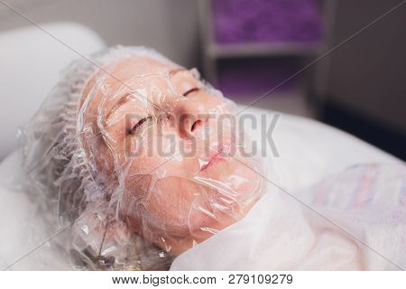 oriental girl with a transparent film before the procedure of skin steaming. biorevitalization preparation. poster