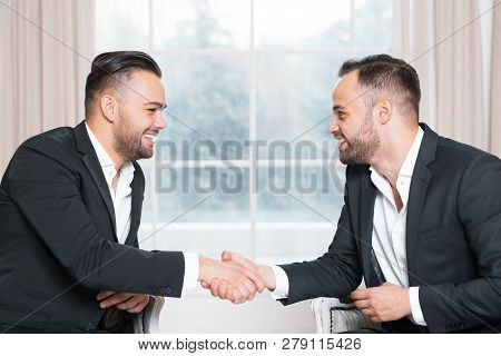 Happy Businessmen Shaking Hands At The Meeting Over Background Of Window.