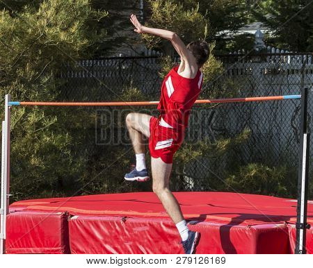 A High School Track And Field High Jumper Is Taking Off From The Ground As He Attempts To Jump Over