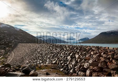 Rock armoured dam at Styggevatnet glacial lake with Austdalsbreen glacier seen in background, Jostedalsbreen National Park, Sogn og Fjordane, Norway, Scandinavia