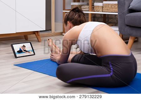 Athletic Woman Doing Stretching Exercise By Looking At Video On Digital Tablet