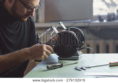 Master Works For Grinding Machine. Man With Glasses Handles Part. Working Process. Sparks Fly.
