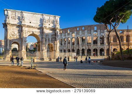 Rome, Italy - January 11, 2019: People at the Arch of Constantine and the Colosseum in Rome at sunrise, Italy