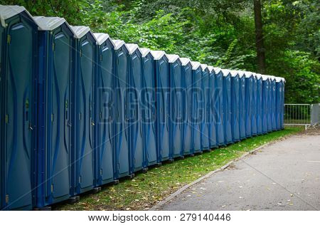 Bio public toilets at a park. Locked, portable chemical lavatories that provide privacy and hygiene. Nature background.