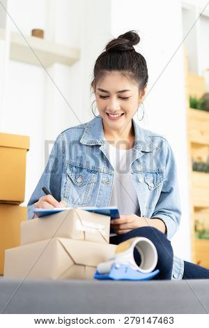 Young Asian Casual Woman Working Small Business Online Packing Her Check Order In Clipboard. Teenage