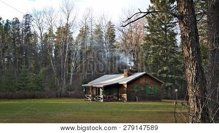 Smoke From Fireplace Rises From The Chimney Of A Cozy Rustic Hunting Cabin In The Woods. Beautiful P