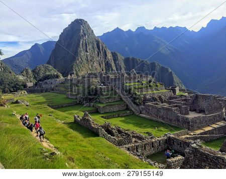 Machu Picchu, Peru - May 10th, 2016: A Small Crowd Of Tourists Admire The Incredible Sights Of Machu
