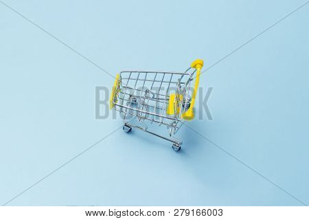 Shopping Cart From The Supermarket On An Isolated Blue Background. Shopping In The Mall, Shop, Shopp