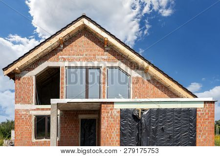 Photo of incomplete brick building with plastic windows on exterior against beautiful sky poster