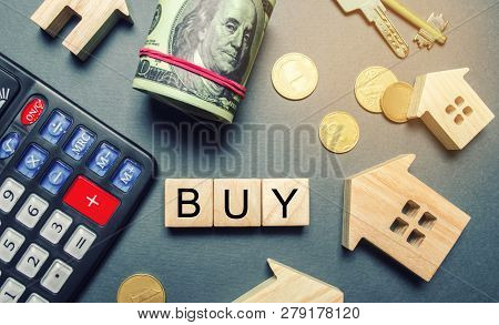 Wooden Houses, A Calculator, Keys, Coins And Blocks With The Word Buy. Buying A House Or Apartment.