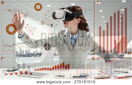 Beautiful And Young Business Woman In Suit Using Virtual Reality Headset With Digital Media Structur