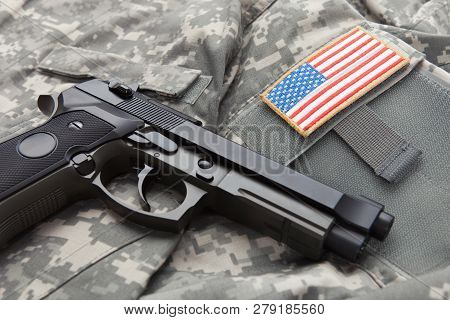 Handgun Over Usa Solder's Uniform With Shoulder Patch On It