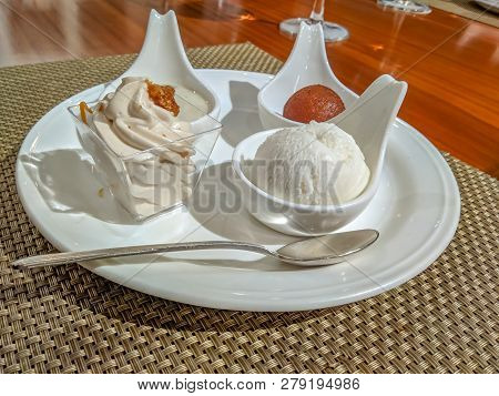 Indian sweets gulab jamun, rasgulla, payesh and cream servered in style on a wooden table poster