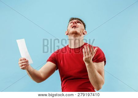 Young Boy With A Surprised Unhappy Failure Expression Bet Slip On Blue Studio Background. Human Faci