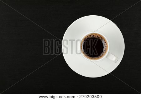 Close Up One White Cup Full Of Instant Coffee On Saucer Over Black Chalkboard Background, Elevated T
