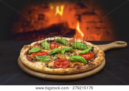 Traditional Baked Pizza On Background Of Blurred Brick Oven Fire
