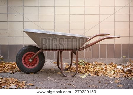 Wheelbarrow And Autumn Leaves In Front Of A Wall