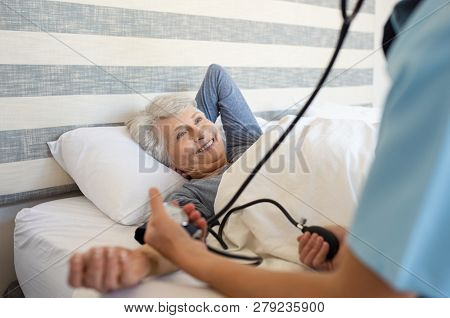 Nurse measuring blood pressure of senior woman with stethoscope and pressure machine at home. Happy mature woman lying on bed while getting blood pressure by doctor. Doctor taking care of old patient.