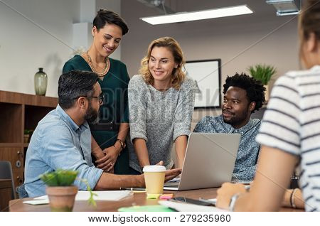 Multiethnic business people talking and smiling during meeting in office. Mature middle eastern man explaining proposal. Happy businessman showing project and marketing strategy on laptop to colleague