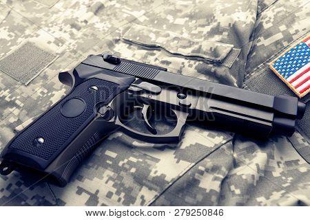 Handgun Over American Solder's Uniform With Shoulder Patch On It