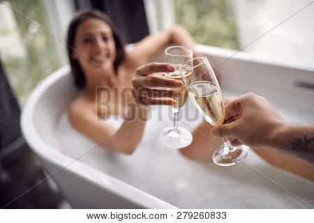 drinking champagne in the bathtub- young couple relaxing together in the bathtub