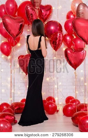 Valentine's Day Concept - Back View Of Beautiful Woman In Black Long Dress With Heart-shaped Balloon