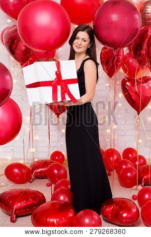 Valentine's Day Concept - Middle Aged Beautiful Woman In Long Black Dress With Big Gift Box And Red