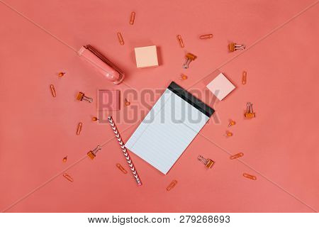 Blank White Note Pad Paper, Pencil, Stapler, Thumb Tacks, Paper Clips, And Adhesive Paper Over Coral