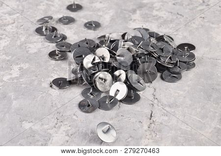 Metal pushpins on a gray concrete table poster