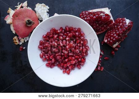Hite Plate With Pomegranate Fruit Next To Pomegranate Pieces And Pomegranate Peel On A Dark Backgrou