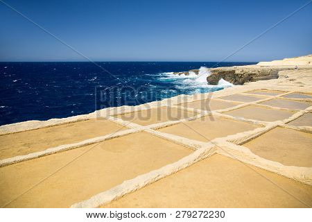 Deep Blue Sea, Horizon And Sky With Yellow-brown Sand Stone Shore Foreground. Salt Ponds In Gozo Isl