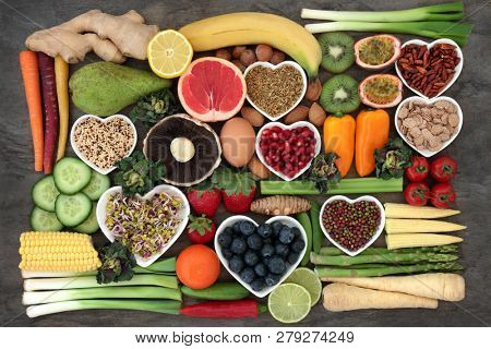 Super food concept for a healthy diet with fruit and vegetables, dairy, spices, nuts, legumes, cereals and grains, high in antioxidants, anthocyanins, dietary fibre and vitamins. poster