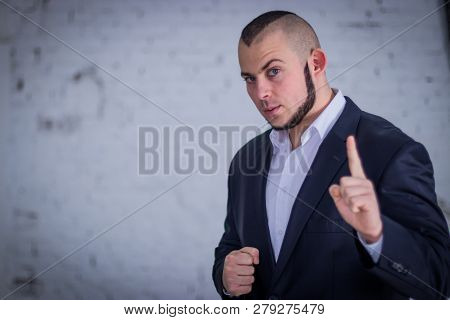 Strong man, bodyguard in a suit against the backdrop of the wall. poster