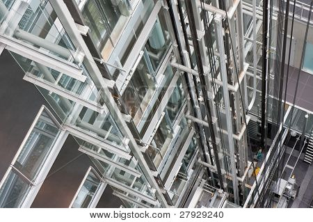 Looking down in an open steel lift shaft in a modern buildin poster