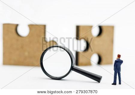 Miniature People: Businessman Standing With Magnifying Glass And Jigsaw Puzzle. Searching Concept: