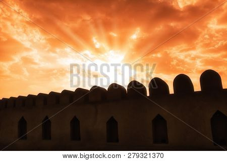 Nizwa Fort Walls Silhouettes And Red Sky With Rays That Pierce The Sky