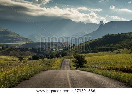 A road leading towards the Royal Natal National Park and the Amphitheatre mountain at golden hour, Drakensberg, South Africa poster