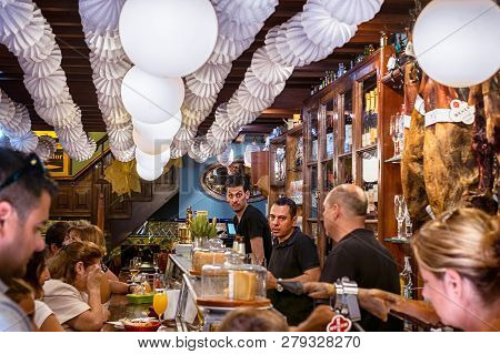 Malaga, Spain - August 12, 2018. People Drinking And Eating At Traditional Tapas Bar With Dry-cured