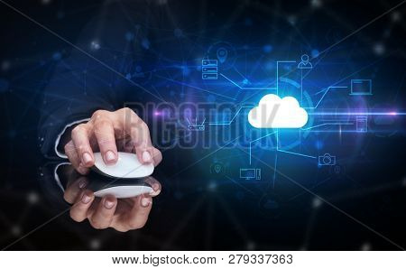 Hand using wireless mouse in a dark environment with cloud technology and online storage concept