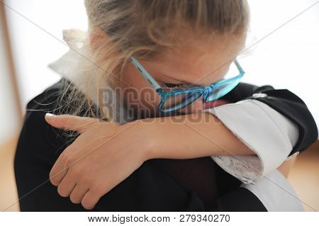 Upset Small Girl In Black Dress In Blue Glasses Sitting Indoors Difficulty