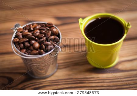 Full Green Bucket Of Black Coffee Near Zinked Metal Bucket With Handle Full Of Roasted Coffee Beans
