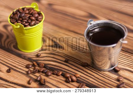 Full Zinked Bucket Of Black Coffee Near Scattered Lot Of Roasted Beans And Green Metal Bucket With H