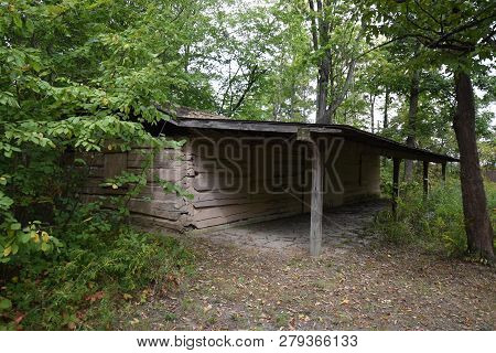 Abandoned Old Wooden House Cabin In The Woods. View Of Old Weathered Wooden With Front Deck Porch Su