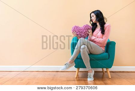 Woman Holding A Heart Cushion In Valentines Day Theme In A Blue Chair
