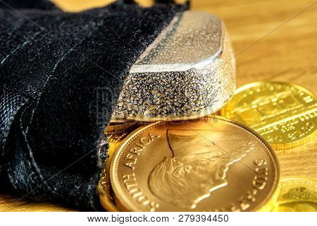 Closeup Of Golden Coins And Silver Brick Falling Out Of Black Moneybag And Laying On Wooden Backgrou