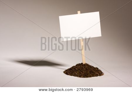 Blank white sign in mound of dirt ready for your own message. poster