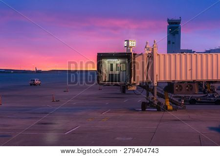 Jetway Doors On And Airport Runway At Sunrise With Flight Control Tower In The Background